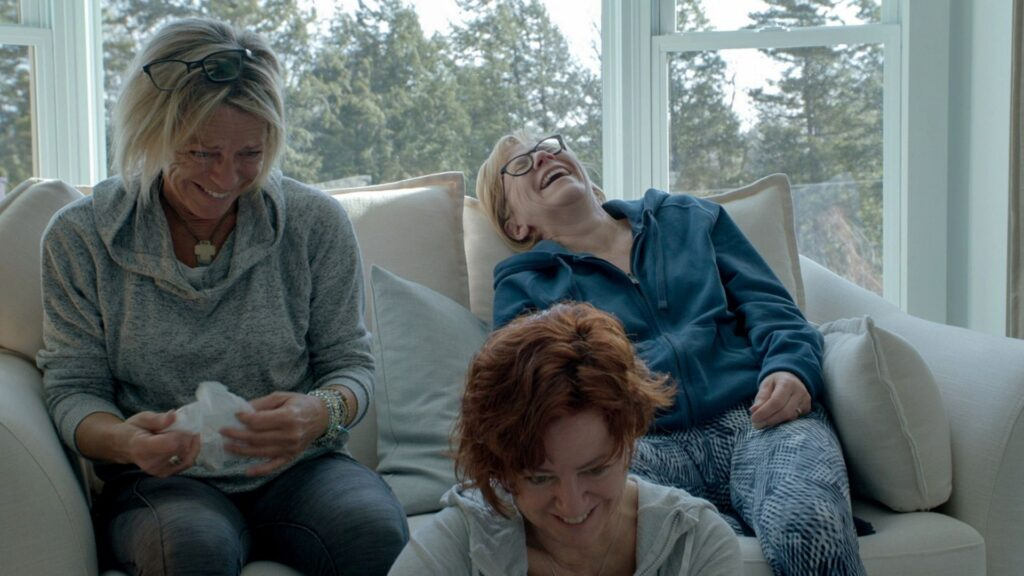 3 women sitting on a sofa laughing